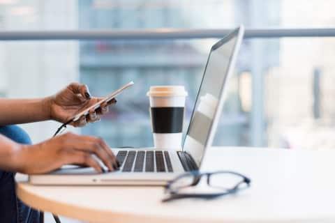 Vrouw bekijkt social media foto's en berichten op laptop en smartphone